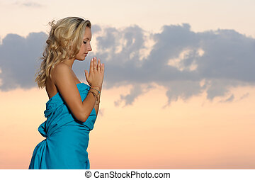 praise - young blond girl praying outdoors at evening time