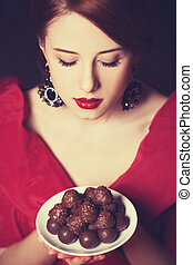 Beautiful redhead women with candy. Photo in retro style.