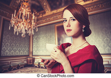 Beautiful redhead women with cup of tea. Photo in old color...