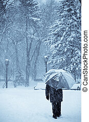 let it snow - lonely old man with umbrella walking under the...