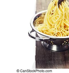 spaghetti in colander over white