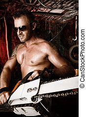hard work - Expressive handsome muscular man with a chainsaw...