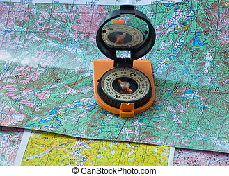 Compass and map. - Magnetic compass in a red-black housing,...