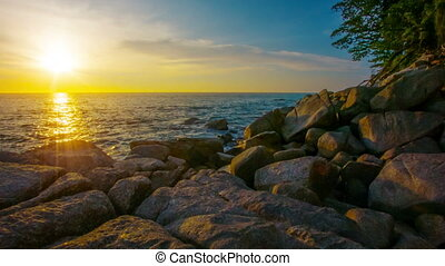 Tropical sea with stones and trees at sunset. Thailand. Kamala Beach