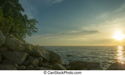 Rocky shore of tropical ocean at sunset