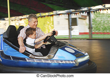 In the summer park rides on my grandfather with his grandson...