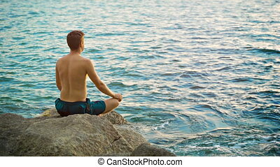 Man practicing yoga on the seashore