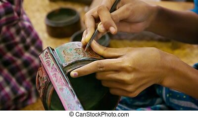 Burma. Artist makes pattern on the product in the workshop -...