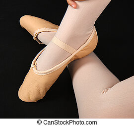 Detail of the feet of a dancer with demi-pointe on black...