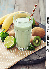 Banana smoothie with kiwi, lime and mint on wooden...