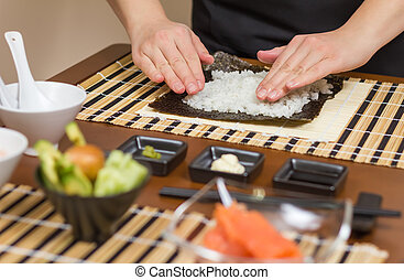 Woman chef filling japanese sushi rolls with rice - Hands of...