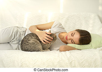 Girl with cat on light background