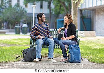 Students Sitting On Bench At University Campus - Happy male...