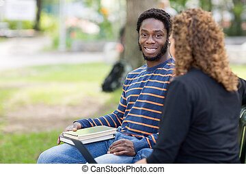 Male Student Sitting With Female Friend On Campus - Portrait...