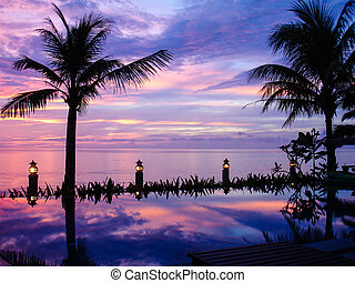 sunset over the Andaman Sea view from an infinite pool -...