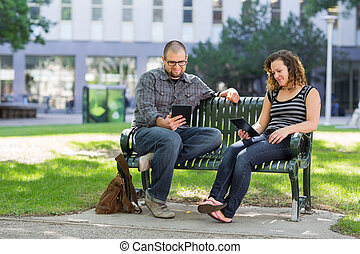Students Using Digital Tablet On Bench At Campus - Male and...