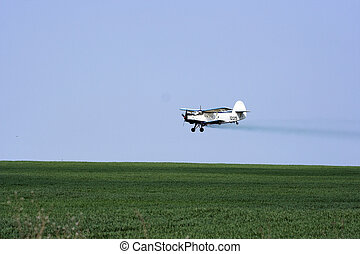 airplane - low flying crop duster  over field.
