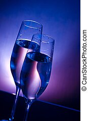 champagne flutes on bar table on dark blue and violet light...