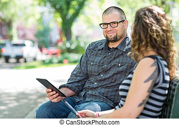 Smiling University Student Sitting With Friend On Campus