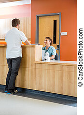 Patient Conversing With Nurse At Reception Desk - Full...