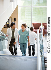 Doctor And Nurse Discussing While Walking On Stairs - Doctor...