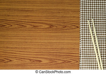 chopsticks with kitchen towel on wood background