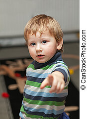 Little boy pointing at camera