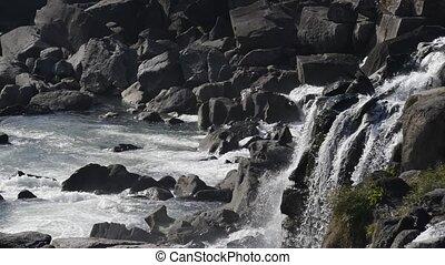 Splashing waterfall flowing through the stacked rocks