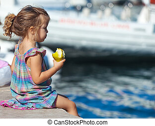 Little blond girl sits on the dock