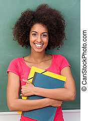 Beautiful young African American student clasping her files...