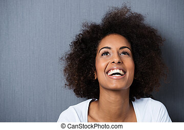 Laughing African American woman with an afro hairstyle and...