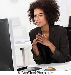 Beautiful young African American businesswoman sitting at...