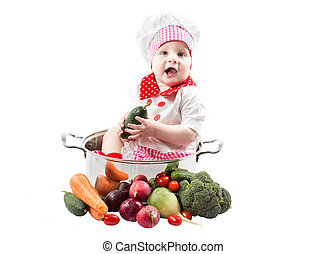 Baby cook girl wearing chef hat with fresh vegetables and...
