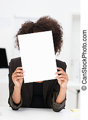 Businesswoman hiding behind a blank sheet of paper -...