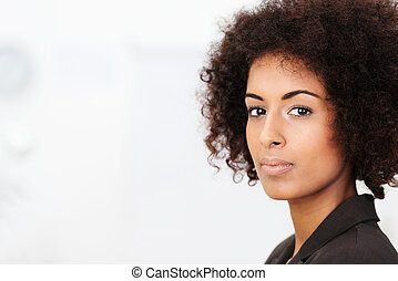 Pensive young African American woman standing looking...