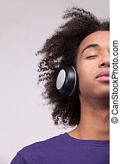 Music lover. Cropped image of teenage African boy in headphones listening to the music and keeping eyes closed while standing isolated on grey background