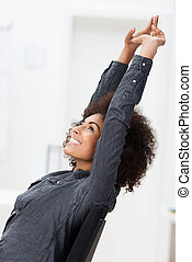 Excited African American businesswoman smiling in jubilation...