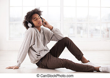 Relaxing with his favorite music. Cheerful African teenager in headphones listening to the music and keeping eyes closed while sitting on the floor