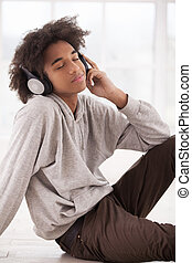 My favorite music. Smiling African teenager in headphones listening to the music and keeping eyes closed while sitting on the floor