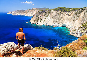 Cliffs of Keri - Young man on top of the cliff at Cape Keri...