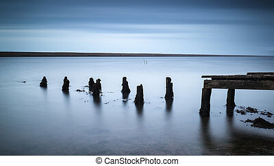 Long exposure landscape of old derelict jetty extending into...