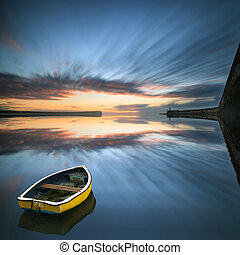 Single boat floating no water during sunrise over ocean with...