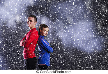 Fitness couple - Young fitness athletes are posing in studio...