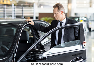 Examining his new car. Confident mature man in formalwear opening the car door at the dealership