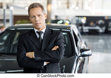 Confident in his choice. Mature grey hair man in formalwear standing in front of car and looking at camera