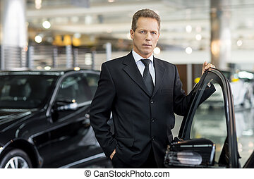 Confident in his choice. Confident grey hair man in formalwear holding hand on opened car door and looking at camera