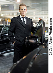 My brand new car. Confident mature grey hair man in formalwear holding hand on opened car door and looking at camera