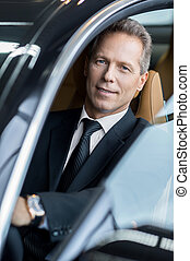 Business trip. Confident senior businessman sitting in car and smiling at camera