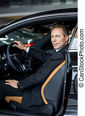 I love my new car. Side view of confident senior man in formalwear sitting in car and smiling at camera