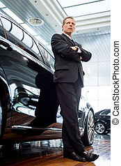Living a luxury life. Low angle view of confident grey hair man in formalwear leaning at the car and looking away